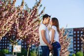 Passion And Love Concept. Man And Woman Kissing In Blooming Garden On Spring Day. Couple Hugs Near S poster
