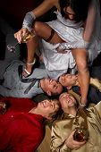 Crazy wedding party in night club. bride making a drunkard of friends of groom