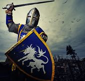 stock photo of swords  - Medieval knight against hill full of crosses - JPG