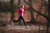 Young woman running outdoors in a city park on a cold fall/winter day (motion blurred image; color t