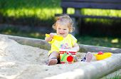 Cute Toddler Girl Playing In Sand On Outdoor Playground. Beautiful Baby Having Fun On Sunny Warm Sum poster