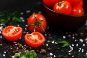 Fresh Sliced Cherry Tomatoes On A Black Background With Spices Coarse Salt And Herbs poster