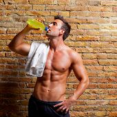 stock photo of muscle man  - muscle shaped man at gym relaxed drinking energy drink - JPG