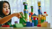 Little Girl In A Colorful Shirt Playing With Construction Toy Blocks Building A Tower . Kids Playing poster