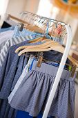 Rack With Clothes Weighing On Hangers. A Lot Of Clothes In Blue Are Ready For Trying. Clothes For Ch poster