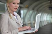 Businesswoman using her laptop at the train station