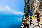 Cycling woman and man riding on bikes at sunrise mountains and Garda lake landscape. Couple cycling  poster