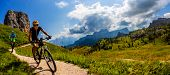 Cycling woman and man riding on bikes in Dolomites mountains landscape. Couple cycling MTB enduro tr poster