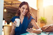 Young beautiful woman holding coffee paper cup and looking at smartphone while sitting at cafeteria. poster