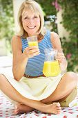 Senior Woman Enjoying Glass Of Orange Juice