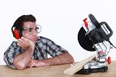 Bored man looking at circular saw