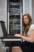 Happy woman running diagnostics on servers in data center