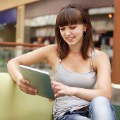 Menina de beleza com tablet PC dentro de casa
