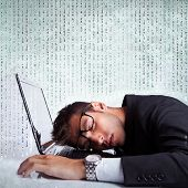 Business man sleeping on a laptop computer on a background full of numbers