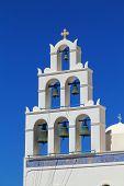 White bell tower of a church St. Irene of Oia, Santorini, Greece.