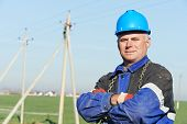 stock photo of utility pole  - Portrait of power line repairman electrician worker on electric post pole work - JPG
