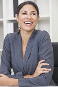 Beautiful happy young Latina Hispanic woman or businesswoman in smart business suit sitting at a des