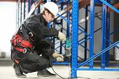 picture of erection  - One warehouse worker in uniform with power tool drilling hole during rack arrangement erection work - JPG