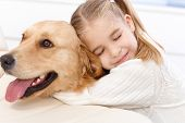 stock photo of cuddling  - Cute little girl hugging golden retriever with love eyes closed - JPG
