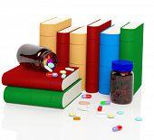 Vitaminas e comprimidos com livros isolados no fundo branco