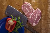 Butcher's still life with a cleaver, slices of raw pork and other stuff.