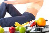 Diet and sport - young woman is doing sit-ups next to a measuring scale, a measuring tape and fruits