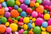 Three different sizes of colorful candies.Colorful background.