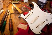 Red electric guitar on guitar repair desk or in a  repair work shop. Neck and pickguard detached. Do