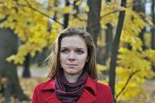 Cute girl in a red coat in the autumn park
