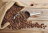 Coffee beans on burlap sack with stainless steel  scoop close-up on wooden table background