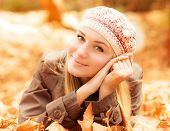 Photo of cute girl laying down on the ground covered dry autumnal foliage in beautiful park in sunny day