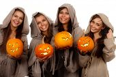 Four smiling nuns in cassocks holding halloween pumpkins