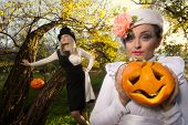 Halloween concept: sexy ladies vampire with halloween pumpkins in forest
