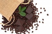 Coffee beans in a hessian drawstring sack and loose with leaf sprigs and dark chocolate over white b