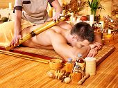Man getting bamboo massage. Female therapist.