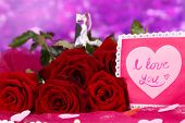 Beautiful bouquet of roses with valentine on pink fabric on purple background close-up