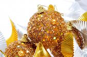 some golden christmas balls and undulating golden and silver garland on a white background