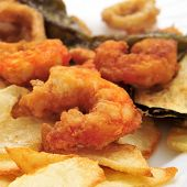 closeup of a plate with battered and fried shrimps served as tapas with potato chips