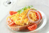 bread whit scrabled eggs decorated with tomato and onion