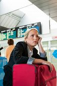 business woman waiting for her departure at the airport. symbolic photo for delays, flight cancellat