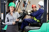 picture of forklift driver  - Portrait of smiling female supervisor with foremen communicating at warehouse - JPG
