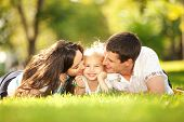 stock photo of daughter  - Happy mother and father kissing their daughter in the park - JPG