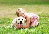 stock photo of caress  - A little blond girl with her pet dog outdooors in park - JPG