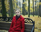 Girl in a red coat in the autumn park sitting on a bench
