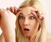image of forehead  - Shocked young woman checking her wrinkles on her forehead - JPG