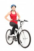 Full length portrait of a female bicyclist posing on a bicycle and giving a thumb up isolated agains