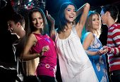 stock photo of night-club  - Portrait of joyful girls laughing while dancing at disco with their boyfriends - JPG