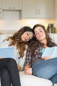 Two girls sleeping on couch taking break from studying on sofa