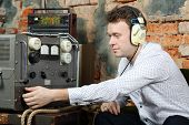 Man in big white headphones configures power source to radio receiver in very old house.