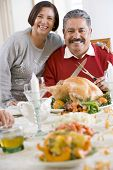 foto of turkey dinner  - Woman With Her Arm Around Her HusbandWho Is Getting Ready To Carve A Turkey - JPG